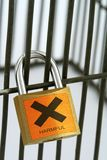 Harmful and banned. Close-up of padlock with harmful sign Royalty Free Stock Photos