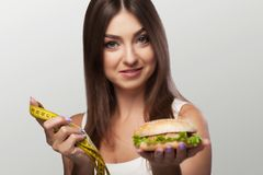Harmful food. A young girl is struggling with overweight and mal. Icious food. The choice between pohudannam and burger. The concept of health and beauty. On a Stock Images