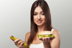 Harmful food. A young girl is struggling with overweight and mal. Icious food. The choice between pohudannam and burger. The concept of health and beauty. On a Stock Photography
