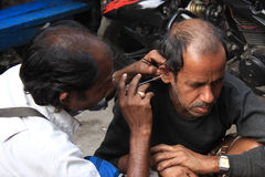 Harmful health consciousness. The man his making his ears cleaned with the help of an iron stick. this is really harmful for health Stock Photography