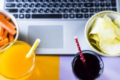 Harmful and healthy snacks. Choose a snack - healthy eating carrots with juice or harmful food chips with cola. Food in the break between working on a laptop Stock Image