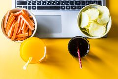 Harmful and healthy snacks. Choose a snack - healthy eating carrots with juice or harmful food chips with cola. Food in the break between working on a laptop Stock Images