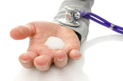 Harmful sugar addiction. Stethoscope on male hand holding white sugar. Sugar addiction concept Stock Images