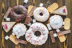Free Harmful Sweet Foods On A Dark Wooden Background. Donuts And Muffins On The Table Pile. Unhealthy Diet And Overweight Stock Photos - 150237283