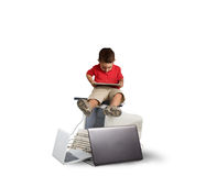 Harmful technology for the growth of the child. Child sitting on a pile of computers. Harmful technology for the growth of the child concept Stock Images