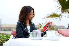 Сharming afro american woman reading novel or book during her recreation time at weekend Stock Photos