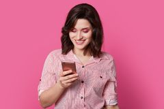 Free Сharming, Beloved Female Person Looks Into Smartphone With Smile In Middle Of Portrait Photography On Isolated Pink Background. Stock Images - 139613904
