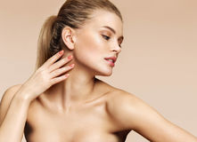 Сharming fashion model posing on beige background. Photo of young blond girl with beautiful makeup. Beauty & Skin care concept Royalty Free Stock Photos