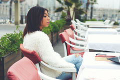 Сharming female hipster sitting on the terrace of sidewalk cafe Royalty Free Stock Image