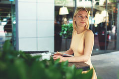 Сharming female hipster waiting someone at sidewalk cafe with green plants Royalty Free Stock Images