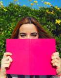 Сharming young woman with pink book held up close to her face Stock Photos