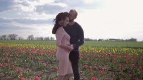 Harmonia com natureza, homem feliz com a menina grávida que espera férias da barriga e da apreciação da fricção do bebê na tulipa video estoque