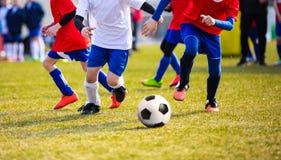 Harmonia do treinamento e de futebol entre equipes da juventude Meninos novos que jogam o fósforo de futebol Fotografia de Stock