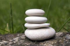 A harmonia e o equilíbrio, seixos simples elevam-se na grama, simplicidade Fotografia de Stock