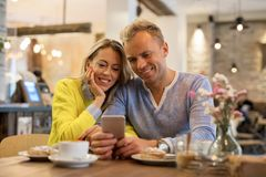Couple looking at smartphone together Stock Images