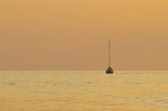 Harmonic sunset with silhouette of a boat Royalty Free Stock Photos