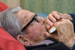 Harmonica de jeu de vieil homme Photographie stock libre de droits