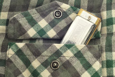 Harmonica in Flannel Shirt Pocket Stock Images