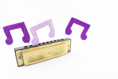 Harmonica and musical figures. Royalty Free Stock Photos