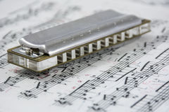 Harmonica is on the musical notes. Steel harmonica is on the musical notes Stock Photos