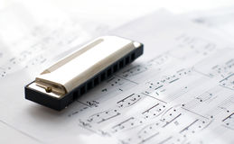 Harmonica on note sheets Stock Images