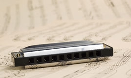 Harmonica with notes Royalty Free Stock Photography