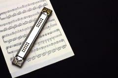Harmonica sur la musique de feuille Images libres de droits