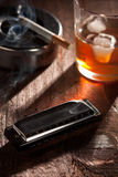 Harmonica with Whiskey and Cigarette. Blues Black Harmonica with a Glass of Whiskey and Smoking Cigarette with Ashtray Royalty Free Stock Photos