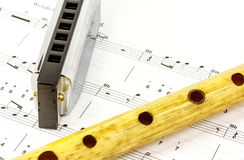 Harmonica and wooden pipe lying on notesheet Stock Photos