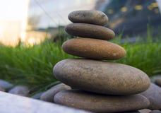 Harmonie und Balance, einfacher Kieselturm im Gras, Einfachheit, fünf Steine Stockbild