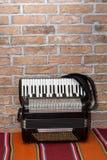 Harmonika door de oude retro bakstenen muur stock foto's