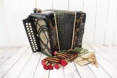 Harmonika, rode anjers, St George lint en oude brieven De dag van de overwinning stock afbeelding