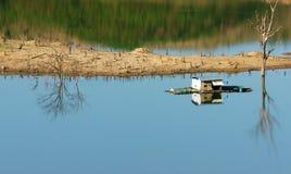 Harmonilandskap som svävar huset, reflexion, torrt träd Arkivbild
