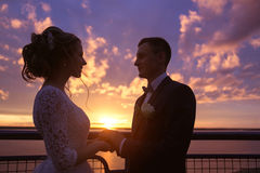 Harmonious beautiful bride and groom holding hands look to each other's eyes at colorful magenta sunset on the Royalty Free Stock Images