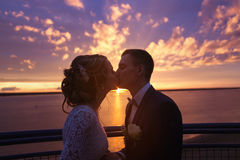 Harmonious beautiful bride and groom holding kissing at colorful magenta sunset on the observation deck. Stock Photography