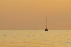 Harmonischer Sonnenuntergang mit Schattenbild eines Bootes Lizenzfreie Stockfotos