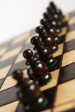 Harmonius team in line. On the chessboard Royalty Free Stock Photos