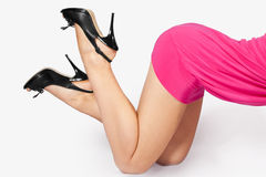 Harmonous feet of the young woman. Thighs and harmonous feet of the young woman in shoes on a heel Royalty Free Stock Image