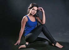 Harmonous girl. The harmonous girl in sportswear sits on a floor against a dark background Stock Photography