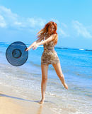 The harmonous girl with a hat against the sea. The girl jumps on an ocean coast Royalty Free Stock Photo