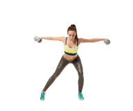 Harmonous girl training with dumbbells at camera. Harmonous female athlete training with dumbbells at camera Stock Photography