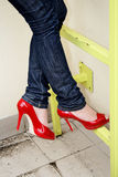 Harmonous legs in jeans and red shoes. On a yellow metal ladder Stock Photography