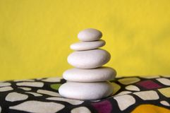 Harmony and balance, cairn, poise stones, rock zen sculpture, three white pebbles. Yellow background royalty free stock images