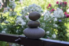 Harmony and balance, cairns, simple poise stones in the garden, rock zen sculpture, dark grey pebbles. Single tower royalty free stock photos