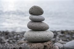Stone cairn tower, poise stones, rock zen sculpture, light grey pebbles. Harmony and balance on coastline, stone cairn tower, poise stones, rock zen sculpture royalty free stock image