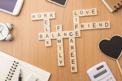 Harmony and balance of life and work on desk. Harmony and balance conception of life, work and family by letters wooden block crossword on desk background Stock Image