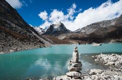 Harmony and balance: Pebble stack and Sacred Lake in Himalayas. Harmony and balance: Pebble stack and Sacred Lake near Gokyo Stock Photography