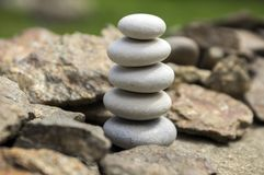 Harmony and balance, simple pebbles tower in another pebbles, simplicity, five stones. Stone cairn on the rock Royalty Free Stock Photography