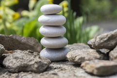 Harmony and balance, simple pebbles tower in another pebbles, simplicity, five stones. Stone cairn on the rock Stock Images