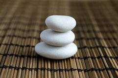 Harmony and balance, simple pebbles tower on dark background. Harmony and balance, simple pebbles tower on dark brown wooden background, simplicity still life Stock Image